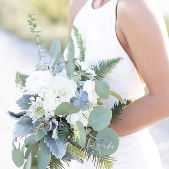 Bride holding a white and sage colored bouquet