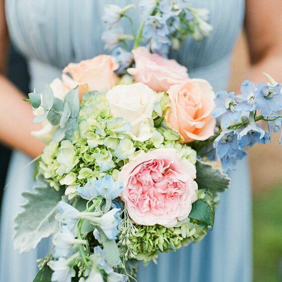 Close up of bouquet of green, blue, peach flowers against a bridesmaids soft blue dress