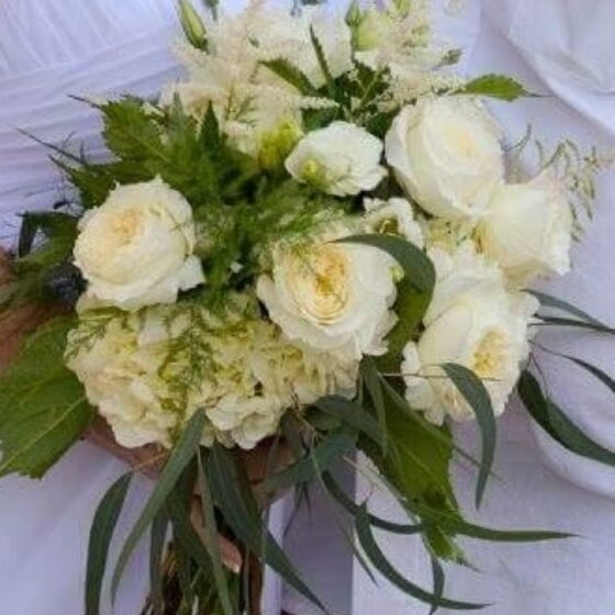 Bouquet of pale yellow and white flowers against a white bridal gown