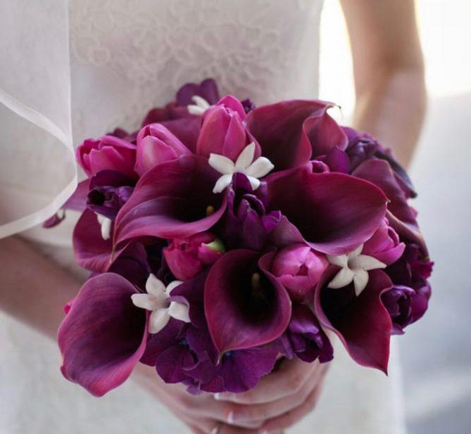 Close up of a bride holding a bouquet of deep fuschia tulips