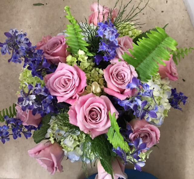 Soft pink roses with lilac coloured flowers and green leaves