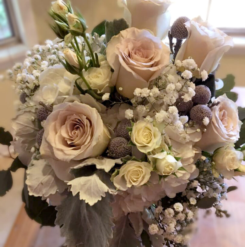 Soft bouquet of pale pink, cream and neutral colored flowers