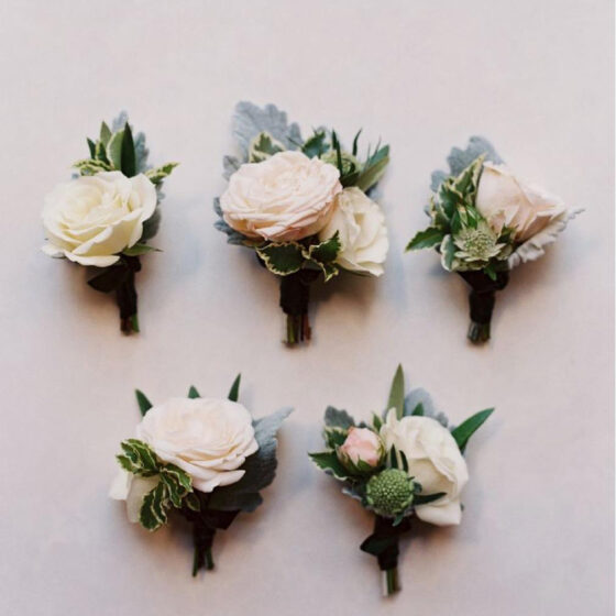 five assorted buttonholes with a soft coloured flower