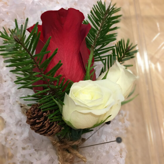 Boutonniere with red and white roses and green leaves