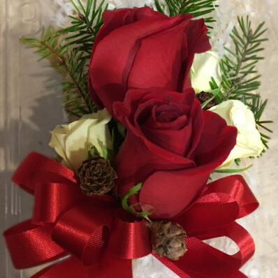 Corsage with deep red roses, deep green fir leaves and a red satin ribbon