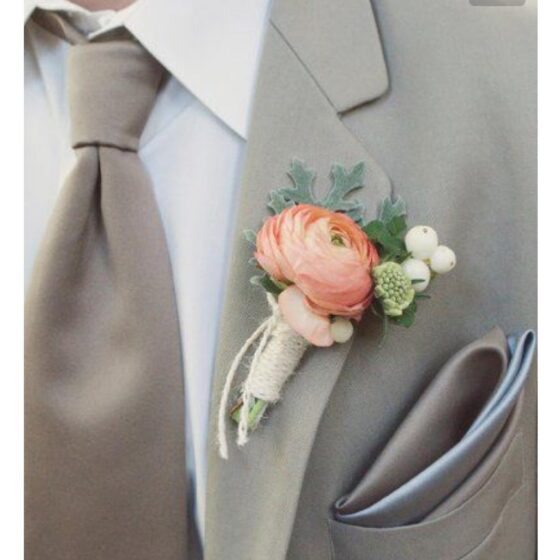 Man in a light grey suit jacket and tie with a boutonniere in peach and soft greens