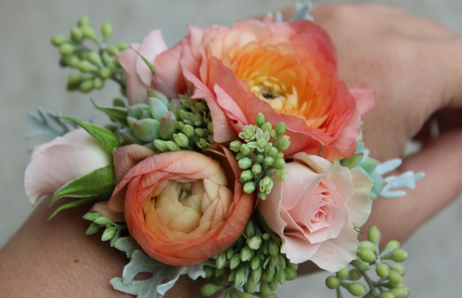 Beautiful corsage on womans wrist with soft peach flowers