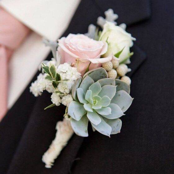 Boutonniere of succulents and soft pink roses on a mans dark suit jacket
