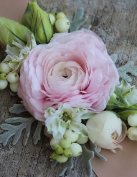 Beautiful corsage with soft pink flowers and light green leaves