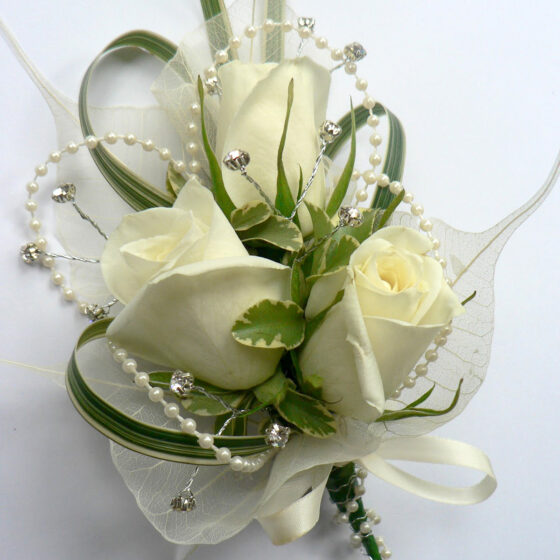 Corsage of white roses, greenery and pearls on a white background