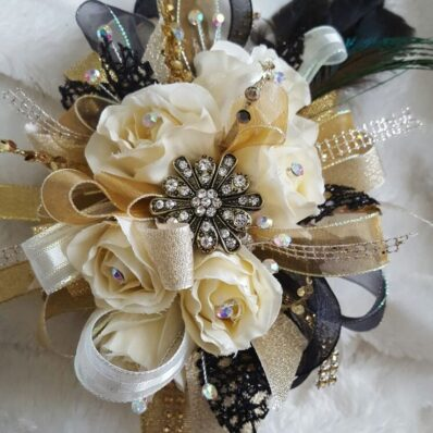 Vintage style corsage with cream flowers, gold and black ribbons and assorted jewels