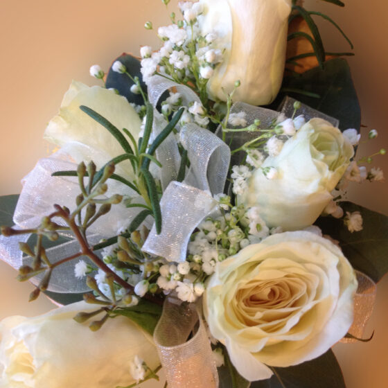 Corsage of white flowers and rosemary sprigs