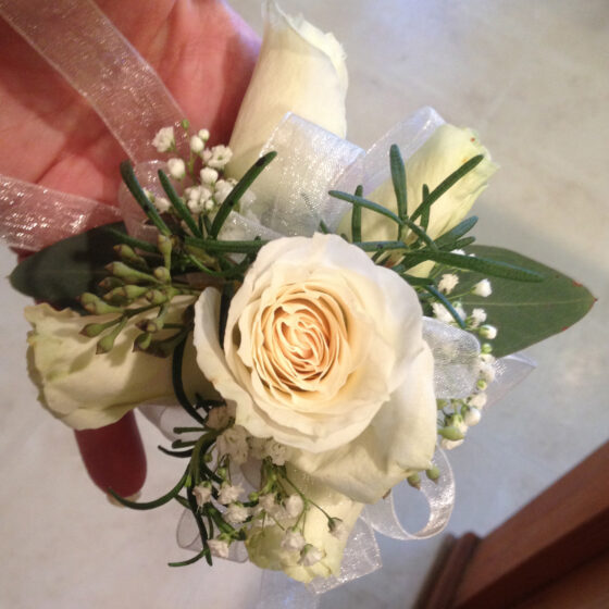 Corsage worn on wrist with white flowers and rosemary sprigs