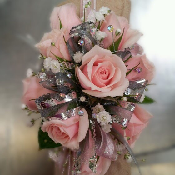 Pretty pink rose corsage on a silver background